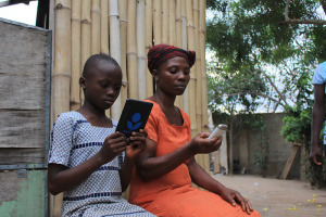 Two young African females reading from their mobile phones