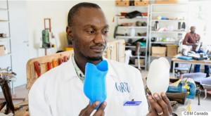 Man holding prosthetics for Uganda